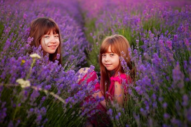 Duas meninas engraçadas jogar em um campo de lavanda Foto Premium