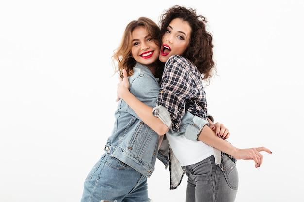 Duas meninas felizes, abraçando-se ao longo da parede branca Foto gratuita