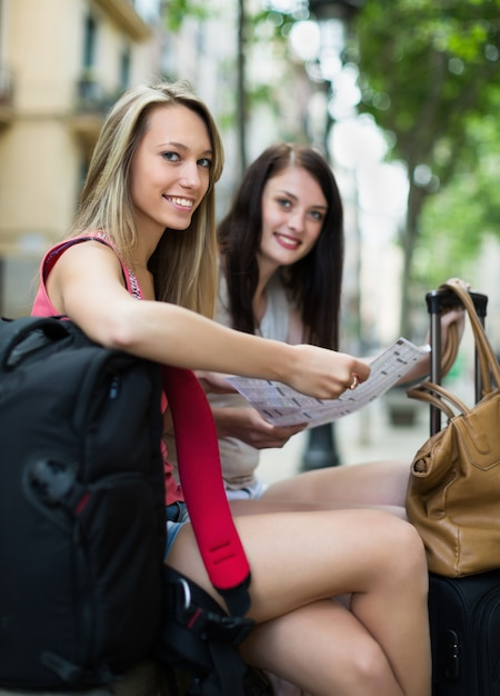 Duas meninas felizes com mapa Foto gratuita