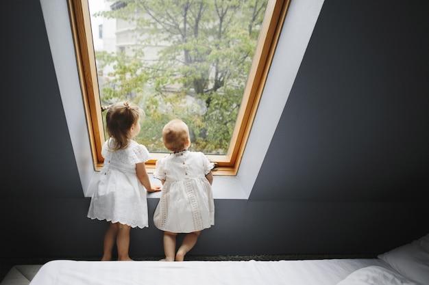 Duas meninas felizes estão olhando alguma coisa na janela Foto gratuita