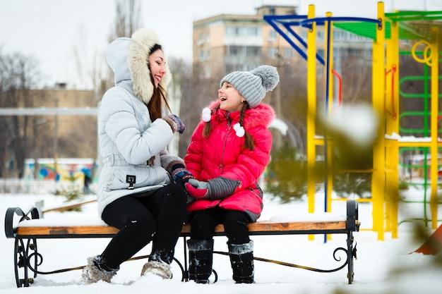 Duas meninas felizes, mãe e filha sentado em um banco em um playground no parque da cidade. Foto Premium