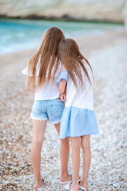 Duas meninas felizes se divertem muito na praia tropical tocando juntos Foto Premium