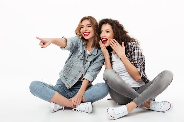 Duas meninas felizes sentados juntos no chão e olhando para longe sobre parede branca Foto gratuita