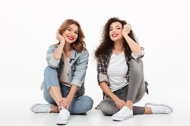 Duas meninas felizes, sentados no chão juntos sobre parede branca Foto gratuita