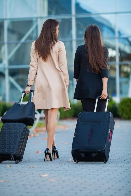 Duas meninas felizes viajando no exterior juntos, carregando bagagem de mala no aeroporto Foto Premium