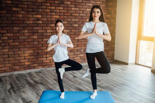 Duas meninas fortes morenas em tempo de manhã, fazendo yoga. com luz do sol. Foto Premium