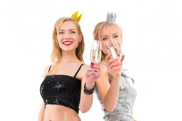 Duas meninas gêmeas posando no estúdio em branco com taças de champanhe e vestidos para uma festa Foto Premium