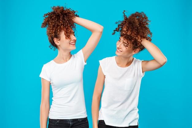 Duas meninas gêmeas segurando o cabelo, brincando sobre parede azul Foto gratuita