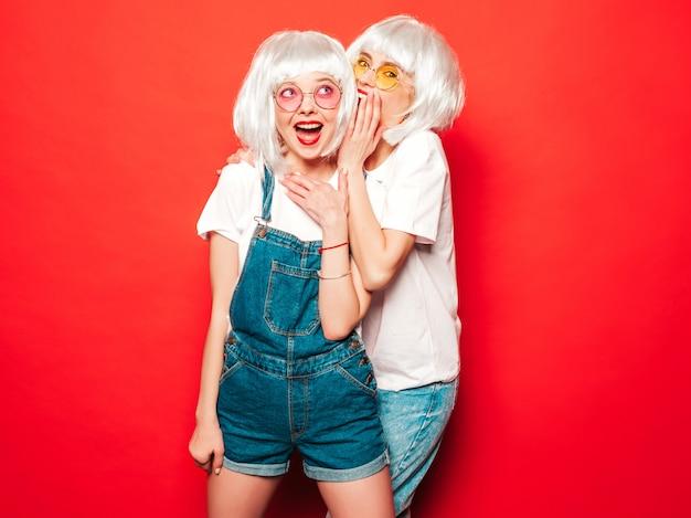 Duas meninas jovens hippie sexy em perucas brancas e lábios vermelhos. mulheres bonitas na moda em roupas de verão. modelos despreocupados posando perto de parede vermelha no verão de estúdio compartilham segredo, fofoca Foto gratuita