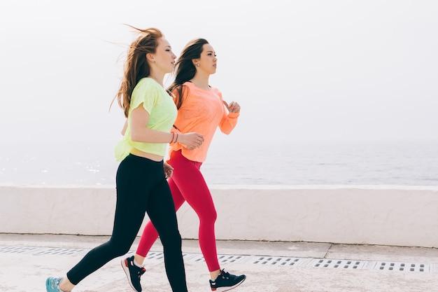 Duas meninas magras no sportswear correndo na praia de manhã Foto Premium