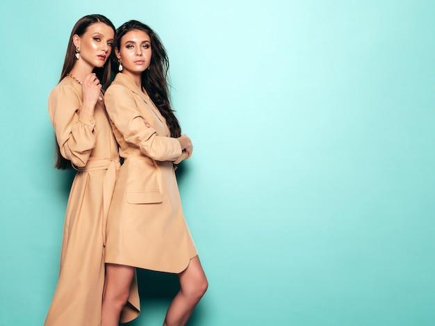 Duas meninas morenas lindas em roupas de verão na moda agradável. mulheres despreocupadas sexy posando perto da parede azul no estúdio Foto gratuita