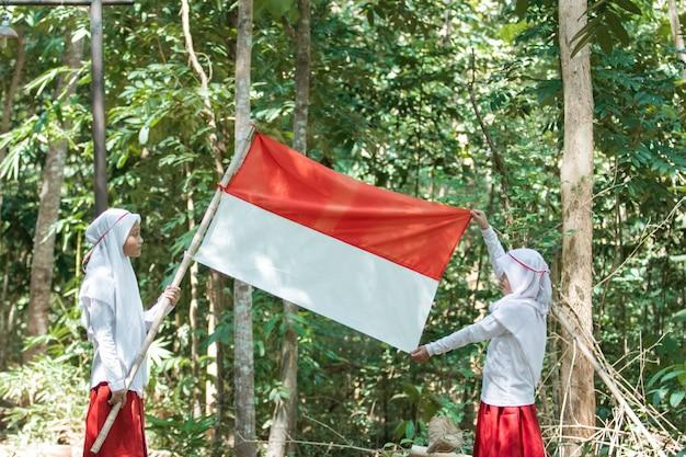 Duas meninas muçulmanas com lenço na cabeça segurando uma bandeira vermelha e branca Foto Premium