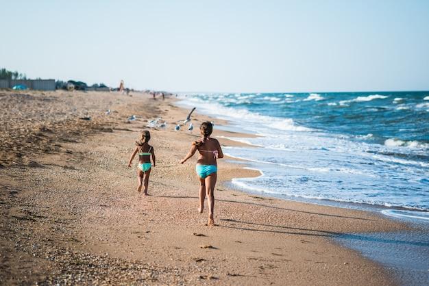 Duas meninas positivas correndo ao longo da praia em um dia quente e ensolarado de verão Foto Premium