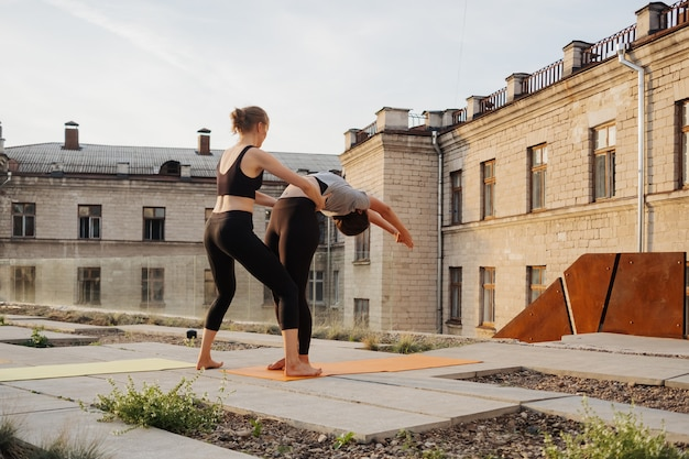Duas meninas praticando alongamento e exercícios de ioga exercitam juntos Foto gratuita