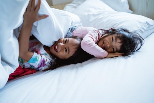 Duas meninas se divertindo e rindo na cama Foto Premium