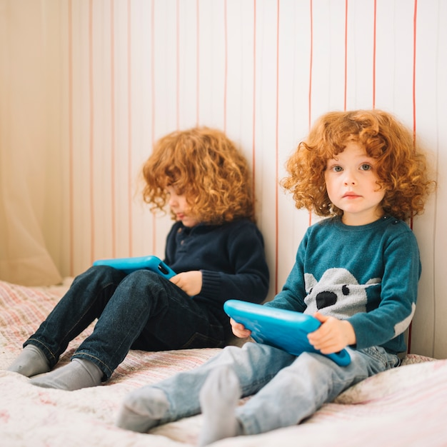 Duas meninas, sentar-se cama, usando, tablete digital Foto gratuita