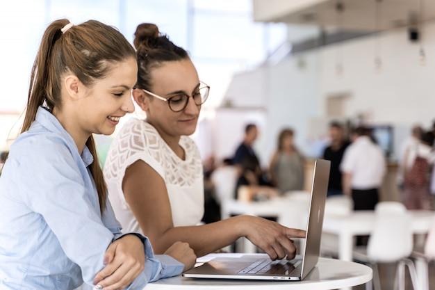Duas meninas trabalhando juntos com um laptop em um coworking Foto Premium