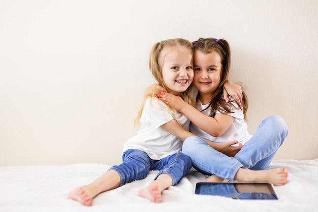 Duas meninas usando um touch pad família, crianças, tecnologia e conceito de casa Foto Premium