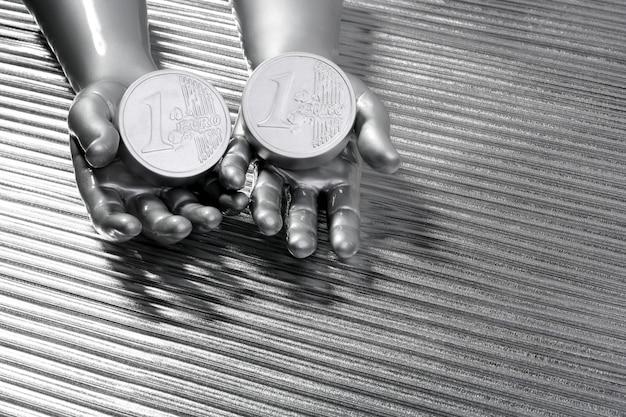 Duas moedas de euro de prata nas mãos do robô futurista Foto Premium