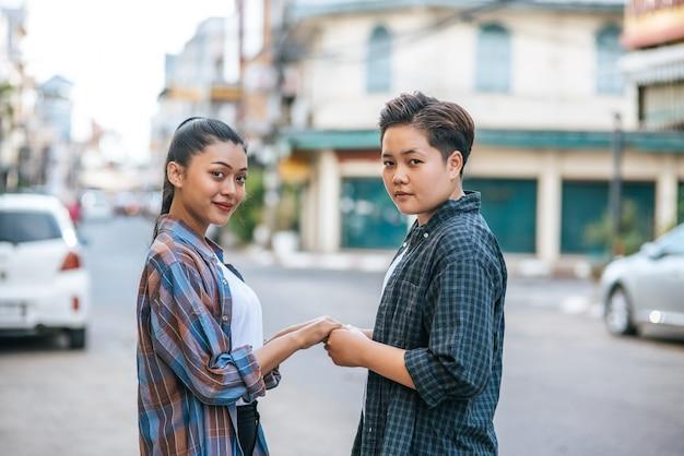 Duas mulheres amorosas em pé e de mãos dadas na rua. Foto gratuita