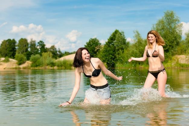 Duas mulheres, aproveitando o dia quente de verão no lago Foto Premium