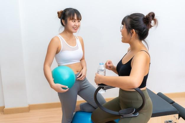 Duas mulheres asiáticas conversando enquanto faziam uma pausa para tomar água durante o exercício de pilates Foto Premium