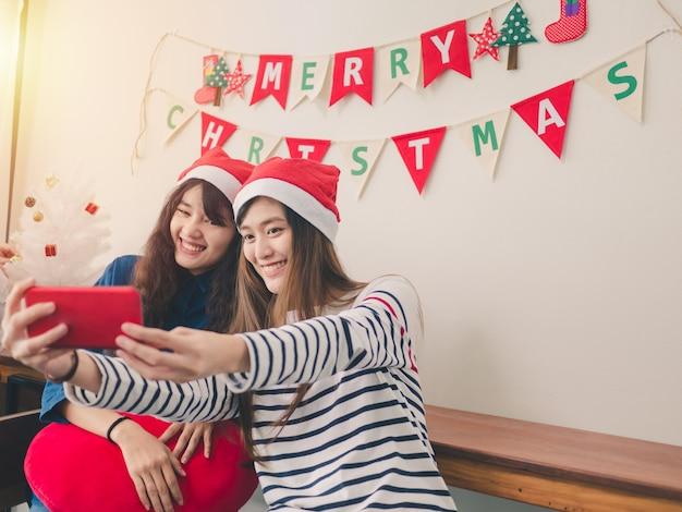 Duas mulheres asiáticas sorrindo pegam fotos na festa de natal Foto Premium