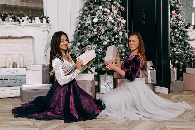 Duas mulheres bonitas e elegantes, felizes e sorridentes. dê uns aos outros presentes de natal em frente à árvore de natal Foto Premium