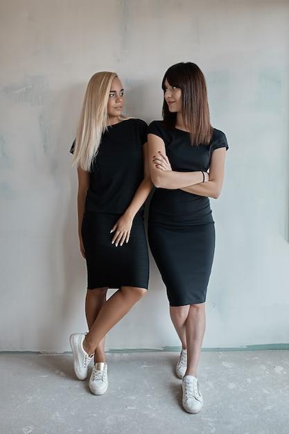Duas mulheres bonitas em vestidos pretos Foto gratuita