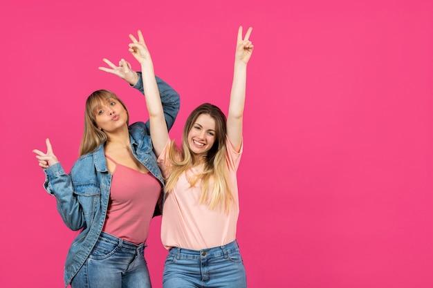 Duas mulheres com as mãos levantadas em fundo rosa Foto gratuita