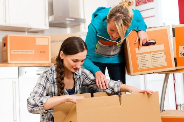 Duas mulheres com caixa de mudança em sua casa Foto Premium