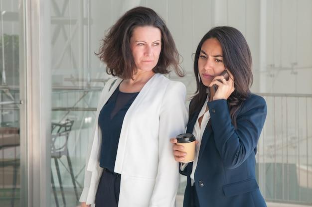 Duas mulheres de negócio sério chamando no telefone e bebendo café Foto gratuita