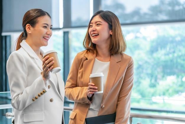 Duas mulheres de negócios asiáticos falando durante o coffee-break no escritório moderno ou espaço de coworking, coffee-break, relaxando e conversando após o tempo de trabalho, o conceito de parceria de negócios e pessoas Foto Premium