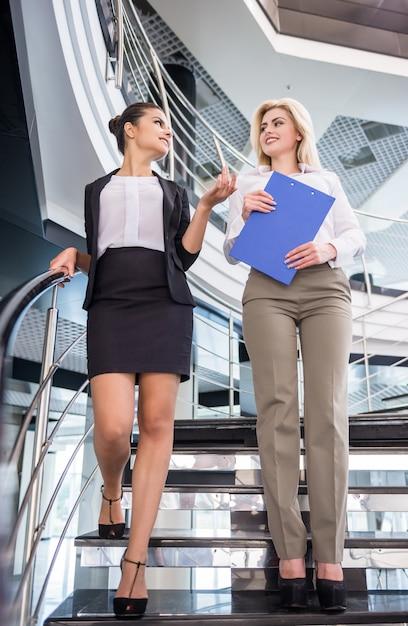 Duas mulheres de negócios atraentes descendo as escadas. Foto Premium
