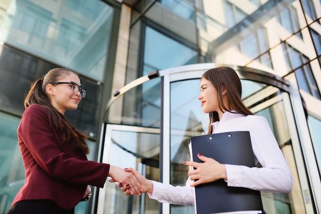 Duas mulheres de negócios bonito jovem, apertando as mãos Foto Premium
