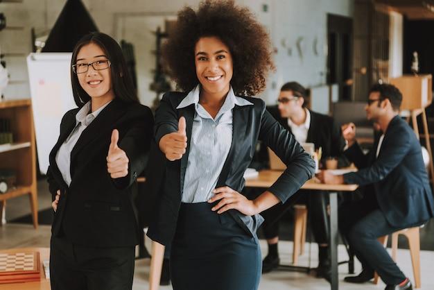 Duas mulheres de negócios estão mostrando os polegares para cima e sorrindo. Foto Premium