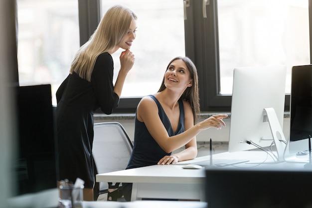 Duas mulheres de negócios sorridentes trabalhando juntos com computador Foto gratuita