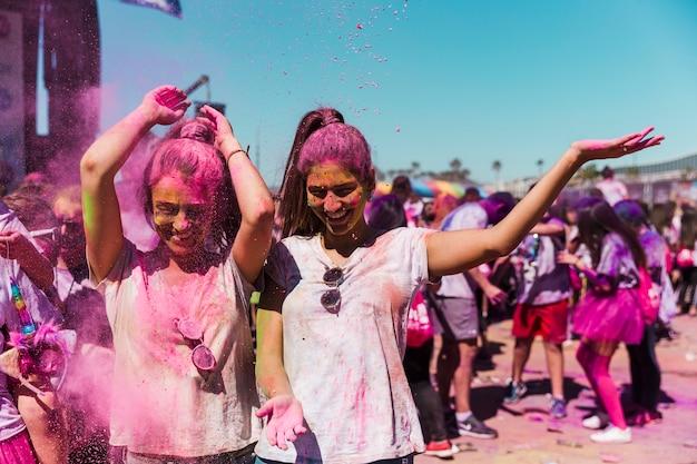 Duas mulheres, desfrutando, e, tocando, com, holi, pó Foto gratuita