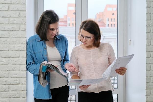 Duas mulheres designer e cliente trabalhando na escolha de tecidos para cortinas, estofados de móveis Foto Premium