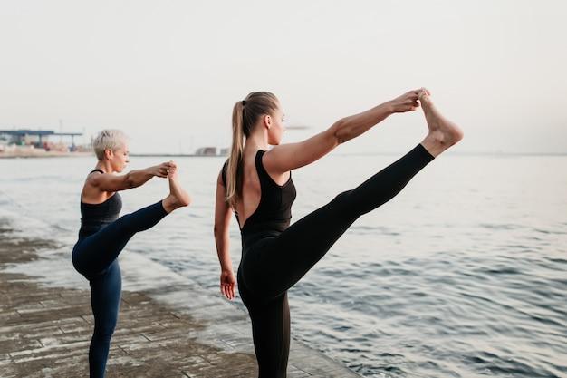 Duas mulheres desportivas aptas esticam as pernas em sincronização na praia Foto Premium