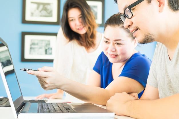 Duas mulheres e um homem estão alegremente olhando para computador no escritório moderno Foto gratuita