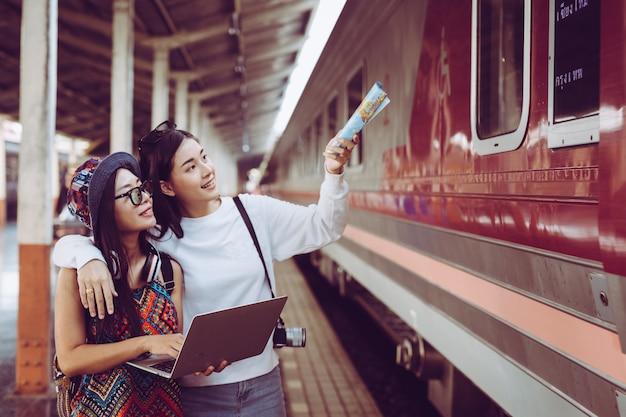 Duas mulheres estão felizes enquanto viajam na estação de trem. conceito de turismo Foto gratuita