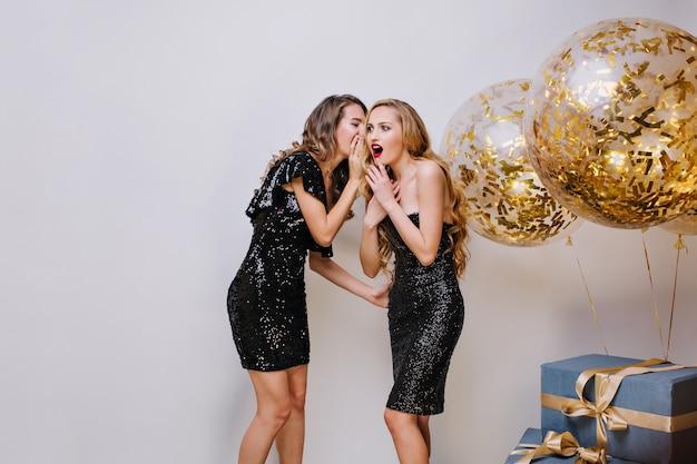 Duas mulheres incríveis em vestidos elegantes de preto, se divertindo no espaço azul. garota fofoqueira, sussurrando, expressando emoções verdadeiras, surpresa Foto gratuita