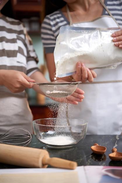 Duas mulheres irreconhecíveis derramando farinha na peneira na cozinha em casa Foto gratuita