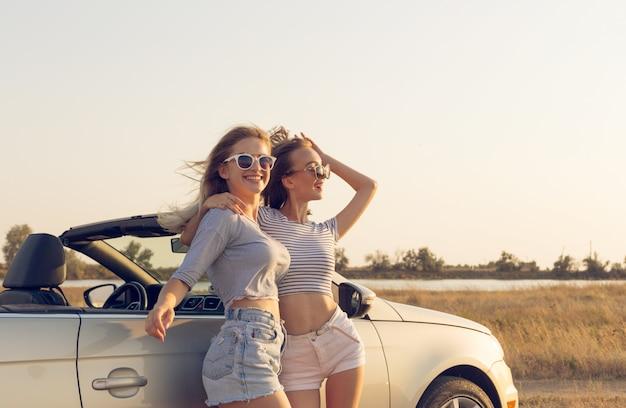 Duas mulheres jovens atraentes perto de um carro conversível Foto Premium