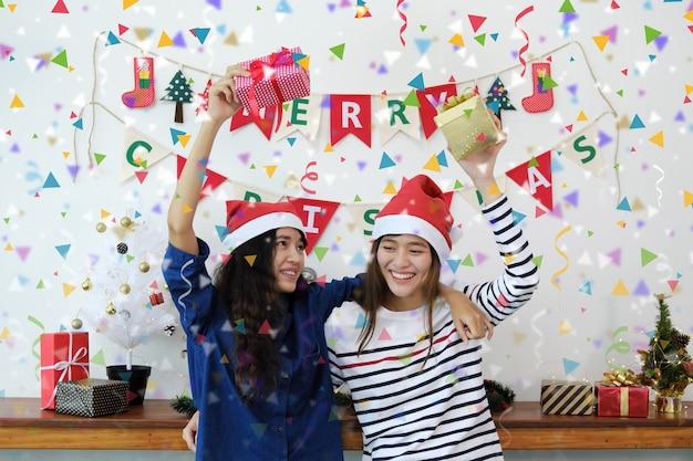 Duas mulheres jovens em chapéus de santa e segurando caixas de presente se divertindo com confetes coloridos na festa de natal. Foto Premium