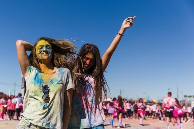 Duas mulheres jovens felizes curtindo e dançando no festival de holi Foto gratuita