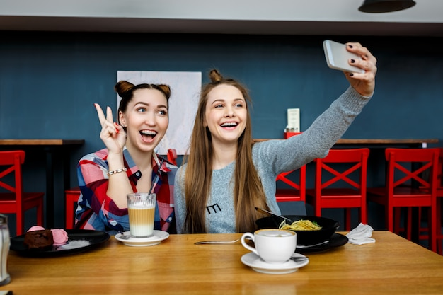 Duas mulheres jovens hipster bonita sentada no café, roupa da moda elegante, férias na europa, estilo de rua, feliz, se divertindo, sorrindo, óculos de sol, olhando para o smartphone, tirando foto de selfie, glamour Foto Premium