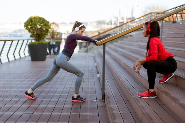 Duas mulheres jovens praticam alongamento ao ar livre Foto Premium
