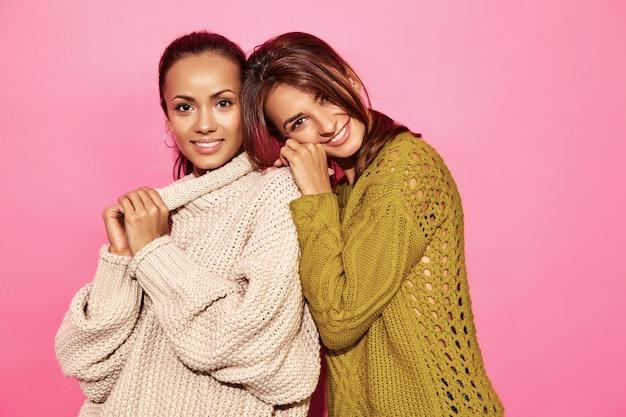 Duas mulheres lindas sorridentes sexy lindas. mulheres gostosas em pé e abraçando em elegantes blusas brancas e verdes, na parede rosa. Foto gratuita